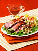 Three slices of roast beef with vegetables and wheat on a bed of rocket