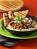 Mediterranean chickpea and vegetables stew on a bed of rice with toasted bread triangles