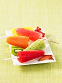 Colourful homemade fruit ice lollies on a square plate