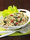 Orzo pasta with white beans, feta and vegetables in an oval dish