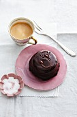 A mini Sachertorte with a cup of coffee