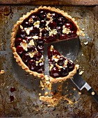 Black cherry tart with frangipane on a baking tray, sliced (seen from above)