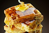 A stack of waffles with butter and dripping honey