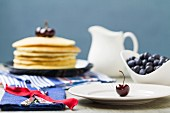 A table laid with blueberries and a stack of pancakes