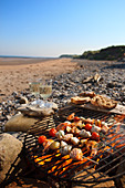 Fish skewers on a barbecue on a beach