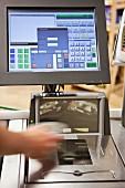 Bildschirmanzeige und Hand beim Kassenscan in einem Supermarkt