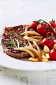 Grilled pork steak with fried onions and cherry tomatoes