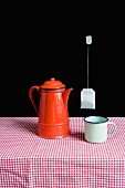 An enamel teapot and a cup on a table with teabag floating in mid-air above them