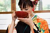 A woman wearing a kimono and eating soup