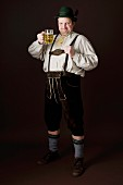 A stereotypical German man wearing lederhosen and holding a tankard of beer