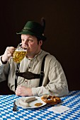 A stereotypical German man wearing lederhosen and eating white sausage with beer