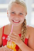 A smiling blond girl with orange juice