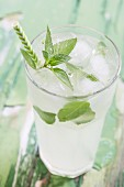 A refreshing drink with ice cubes, mint and a straw