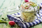 A jar of potato salad with radishes and thyme on a green wooden table