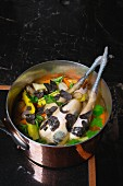 Chicken soup with a whole chicken, black truffles and vegetables in a copper pot