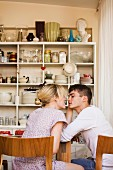 A young couple flirting at a kitchen table with a shelf of crockery in the background