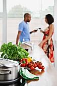 Gemüse und Kräuter und Topf auf Arbeitsfläche und ein junges Paar im Hintergrund