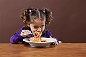 A little girl eating spaghetti with her eyes closed