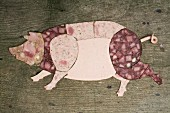 Cold cuts of meat arranged in the shape of a pig on a wooden surface