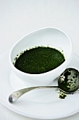 A bowl of mint sauce next to a sauce ladle