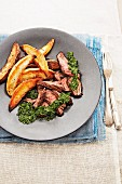 Grilled steak with potato wedges and chimichurri