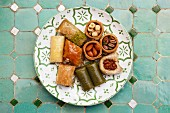 Various baklava and Turkish nut cakes on a ceramic plate