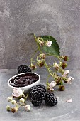 A bowl of blackberry jam, blackberries and blackberry sprig