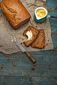 Sliced banana bread with maple syrup, one slice spread with butter
