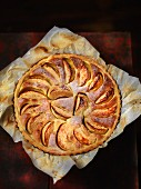 Apple tart with icing sugar on a piece of baking paper