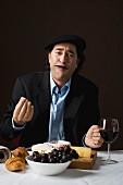 Typisch französischer Mann isst Käse und Trauben