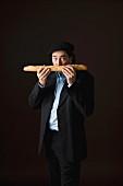 Typisch französischer Mann riecht an einem Baguette