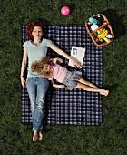 Mutter und Tochter liegen auf einer Picknickdecke auf dem Rasen