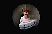A pizza delivery man with pizza boxes seen through a spyhole