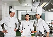 Three chefs joking around in a commercial kitchen