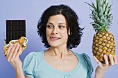 A woman holding a pineapple and a bar of chocolate