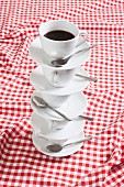 A stack of coffee cups and saucers on a checked tablecloth