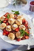 Profiteroles with strawberries on a garden table