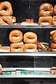 Various bagels on shelves behind a shop window