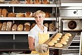 Frau halt Backblech mit frisch gebackenen Brötchen in einer Bäckerei