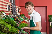 A sales assistant in the vegetable department of a supermarket