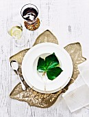 Leaf with hand-written name on white plate and fabric place mat shaped like a leaf arranged on white wooden table