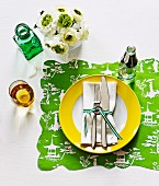 Cutlery and napkin tied with ribbon on plate with yellow edge and place mat made from printed wrapping paper with wavy edge