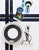 Schwarzweisse Tischdeko mit Kreismustertellern auf gekreuzten Bändern, Besteck mit Schleife und Kinderfoto mit englischem Weihnachtsgruss