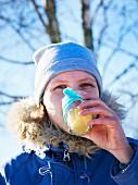 Frau trinkt heiße Limonade beim Winterpicknick