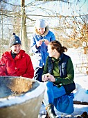 Three women at a winter picnic in Scandinavia