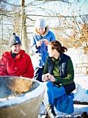 Drei Frauen beim Winterpicknick in Skandinavien
