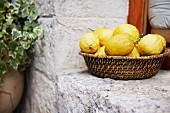 A basket of lemons on a stone windowsill
