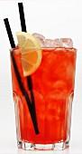 Ein rötlicher Cocktail mit Eis vor weißem Hintergrund