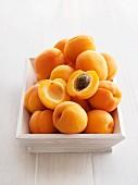 Ein Haufen frische Aprikosen, eine davon halbiert