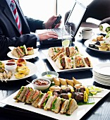 A buffet in a meeting room featuring sandwiches and skewers